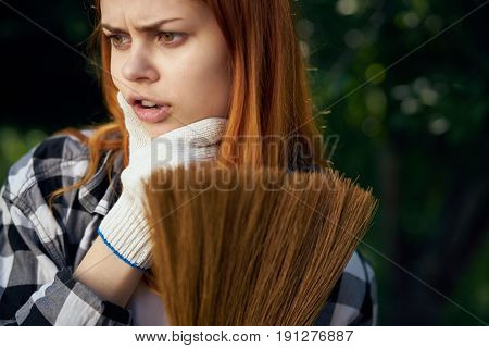 Woman thinking woman looking away, woman holding broom with working gloves.