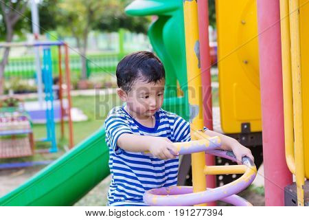 Active Little Child Playing Climbing Spring Metal At School Yard Playground.