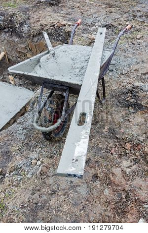 View on Wheelbarrow full of concrete on costruction site.
