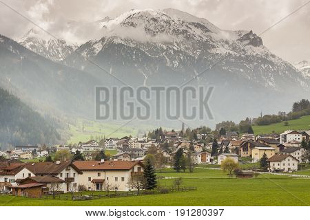View on Mustair village in background big Alps mountains - Switzerland Europe. Spring cloudy day.