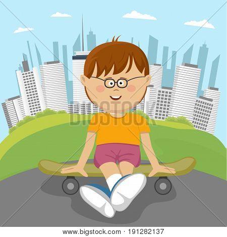 Cute little nerd boy sitting on a skateboard in park in front of downtown