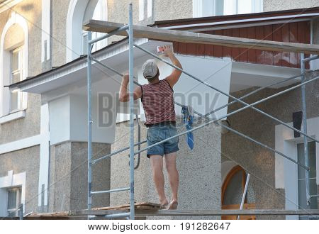 KYIV UKRAINE - JULY 11 2017:  Constructor Install Soffit. Roofing Construction. Soffit Installation and Fascia is Installed on the Underside of Roof Overhangs and Eaves. Roof repair.