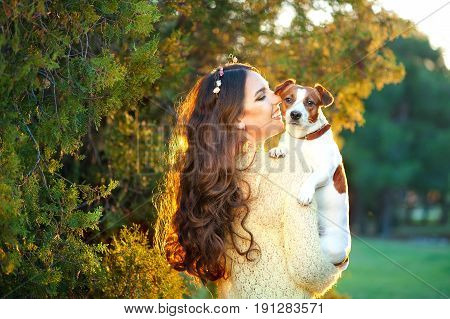 Happy young woman hugging and having fun with her Jack Russell Terrier outdoors