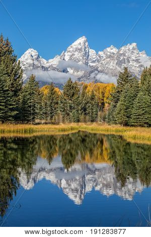 a scenic reflection of the Teton mountains in autumn