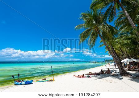 BORACAY, WESTERN VISAYAS, PHILIPPINES - MARCH 27, 2017: Coconut trees makes shady to protect tourists against the sun. Kayak and paddleboard are options for fun at White Beach.