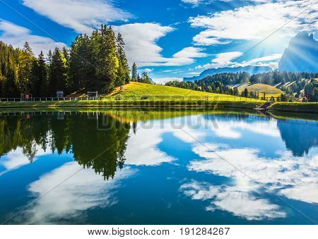 Wonderful small lake reflects the jagged rocks of the Dolomites - World Natural Heritage. Well-known international ski resort in the fall. Concept of active and ecological tourism