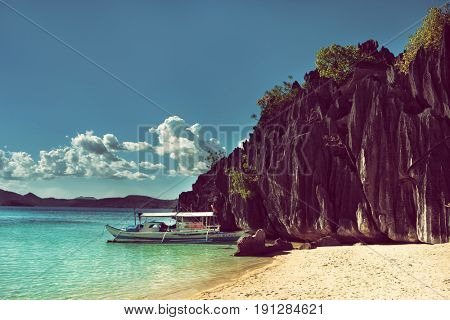 Palawan - May 2017: Boat by tropical beach surrounded by rocks and turquoise sea.
