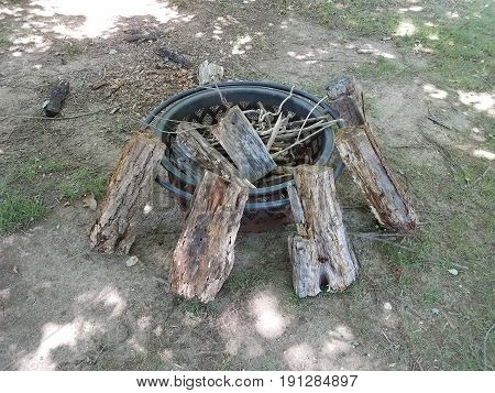 metal fire pit with wood logs on the grass