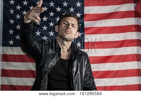 Tough Guy In A Leather Jacket Against The Background Of The American Flag
