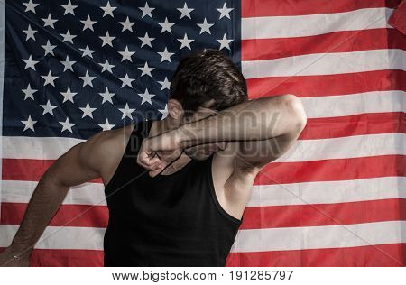 The Man Is A Protecting Hand Over His Face On An American Flag Background,