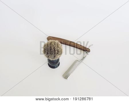 Vintage wood handle straight razor with badger hair brush. Isolated. White background.