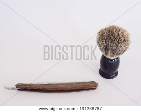Vintage wood handle straight razor with badger hair brush. Isolated. White background. Copy space.