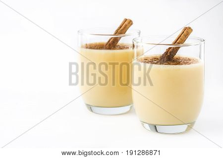 Homemade eggnog with cinnamon isolated on white background. Typical Christmas dessert.