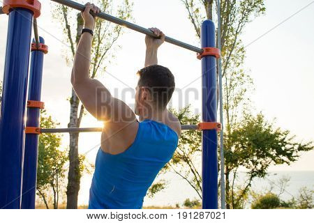 Muscular man doing pull-ups on horizontal bar, training of strongman on outdoor park gym in the morning.