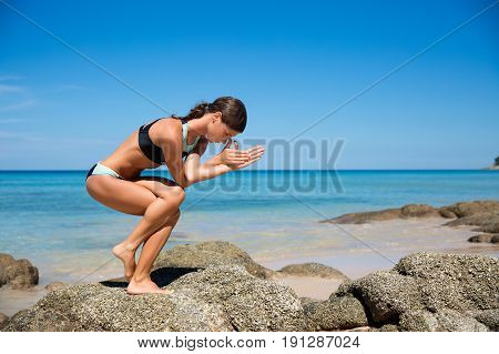 Healthy yoga exercise on the beach slim sporty body training leisure and meditation vacation sport health care concept over natural background blue sky and sea. Ashtanga vinyasa