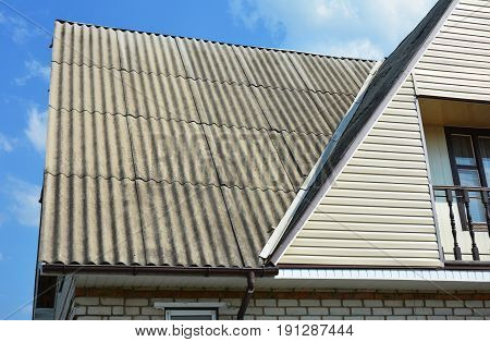 Close up on problem areas for house asbestos roof corner roofing construction. Repair Roof. Guttering Rain gutter asbestos removal. Gable and Valley type of roof construction.