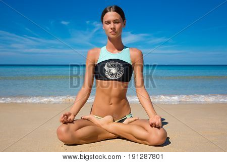 Beautiful sporty fit yogini woman practices yoga asana Virabhadrasana - warrior pose on the beach