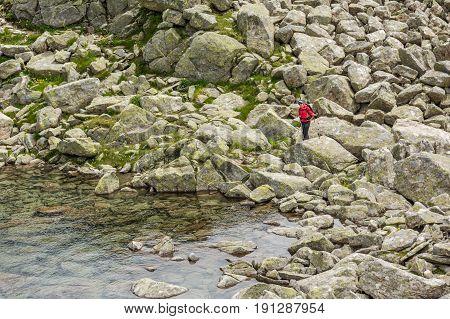 Happy trekker standing on lake shore. Nero Lake above Madonna di Campiglio, Italy.