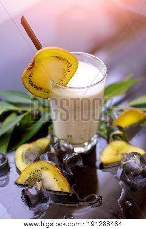 Fruit chocolate milk shake with fresh mint kiwi and ice on the glass table with blurred background