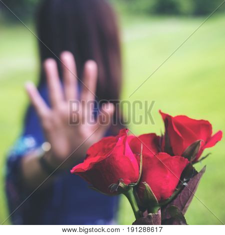 An Asian women rejecting a red rose flower from her boyfriend on Valentine's day with nature and blue sky background