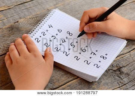Kid solves multiplication examples. Kid holds a marker in his hand and writes answers to multiplication examples in a notebook. Children math education concept