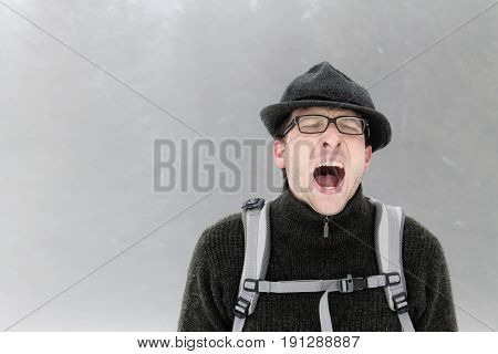 MURNAU AM STAFFELSEE, GERMANY - APRIL 5: A young man with a felt hat is making a funny face while hikink up a mountain on a foggy winterday April 5, 2013, near Murnau am Staffelsee.