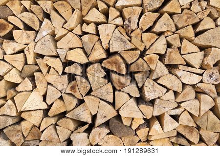 Woodpile made of pieces of wood with weathered, soiled cut surfaces