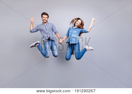 Freedom And Fun, Emotions And Feelings. Cheerful And Playful Couple In Casual Outfits Are Jumping An