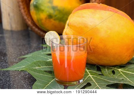 Fresh papaya juice in the glass with papaya fruits and papaya leaf on black stone table.Raw food diet. Selective focus.