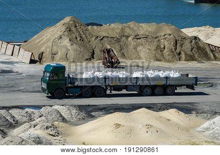 Crane In River Port. Heavy Cranes Unloading Metal To Import. Steel Delivery