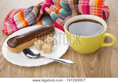 Eclair With Chocolate, Spoon, Lumpy Sugar In Plate, Black Coffee