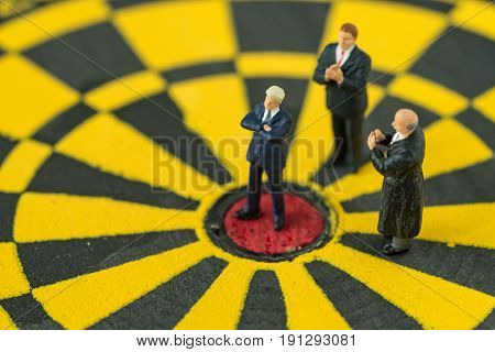 Miniature people small figure businessman standing at the center of dartboard and others clapping as business goal success concept.