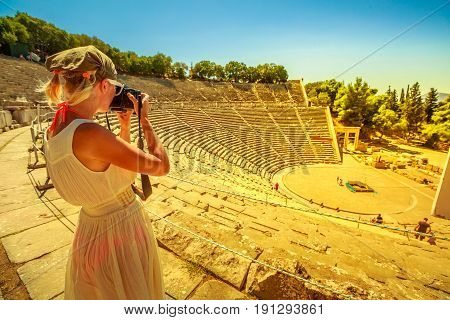 Travel woman photographer takes shot of Archaeological Site, Peloponnese, Greece. Caucasian female photographing Epidaurus amphitheater. European travel destination. Historical heritage. Sunset shot.