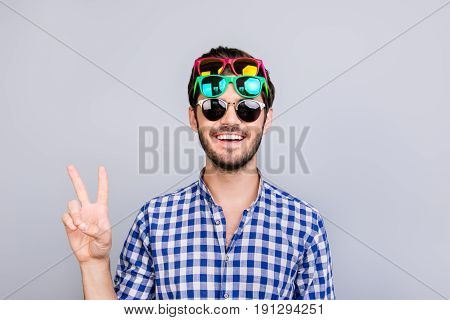Cool! Playful young brunette bearded man in three pairs of bright colorful glasses and checkered casual shirt is fooling around posing and shows v sign smiling on light background