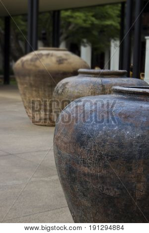 Oversized weathered and aged urns in a courtyard.