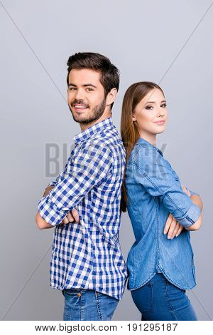 Two Cheerful Young Lovers Are Looking At The Camera And Smile, Standing Back To Back, Wearing Casual