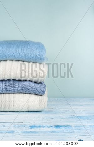 Knitted wool sweaters. Pile of knitted winter, autumn clothes on green, wooden background, sweaters, knitwear, space for text.