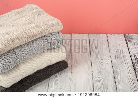 Knitted wool sweaters. Pile of knitted winter, autumn clothes on red, , wooden background, sweaters, knitwear, space for text.
