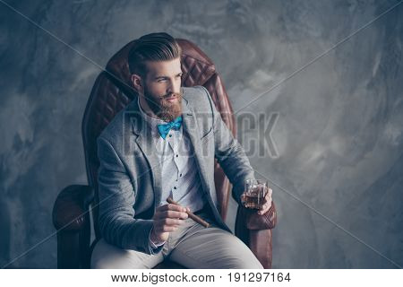 Portrait Of Handsome Elegant Young Red Bearded Man Holding Glass Of Cognac And A Cigar, Sitting And