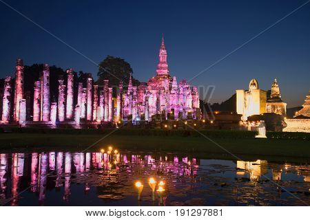 Ruins of the ancient Buddhist temple Wat Mahathat in purple lighting in the late evening. Historical Park of Sukhothai, Thailand