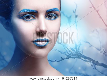 Young woman with creative makeup ant tree branch on background