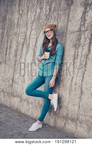 Full Length Of Excited Girl, Standing Near Concrete Wall Outside, Smiling, With Crossed Legs And Hol