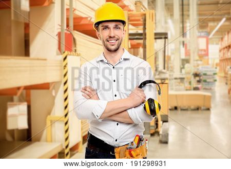 Carpenter with tool belt at storehouse