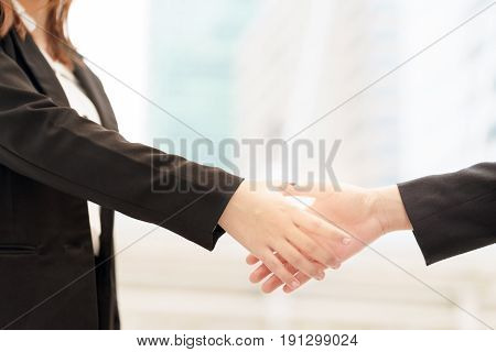 Close up of two smile businesswoman shaking hands on blurred building background