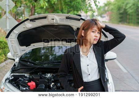 Closeup portrait Stressed woman looking for someone help with opening car hood - car breakdown