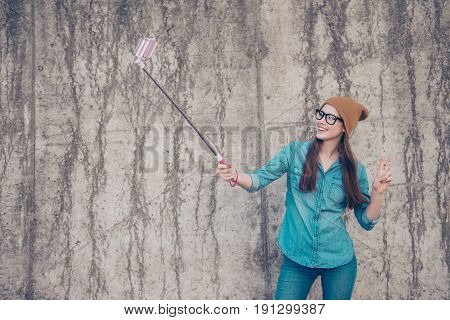 Carefree And Happy, Funky Mood. Cute Young Hipster Is Making Selfie Outdoors On A Camera Of Her Phon