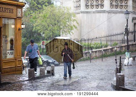 Paris, France - May 12, 2017: A man walking using a parasol as an umbrella