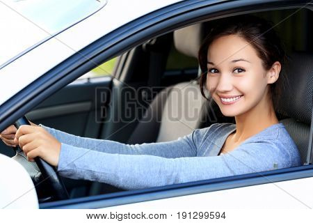 Beautiful woman driver smiling to you from her car