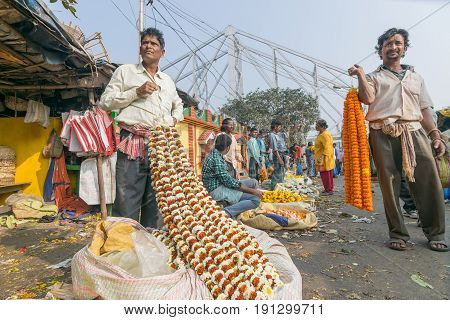 KOLKATA WEST BENGAL / INDIA - FEBRUARY 13TH 2016 : Buying and selling of flowers in crowded and colorful Mallik Ghat or Jagannath ghat flower market in Kolkata. Biggest flower market in Asia.