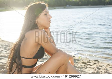 Sea sandy beach. A young slender, suntanned girl is enjoying the bright sun.